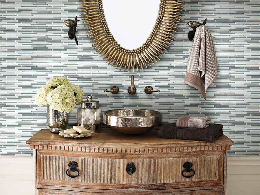 Close up image of a trending 2020 bathroom sink with a tile backsplash, bronze fixtures, and a mirror.